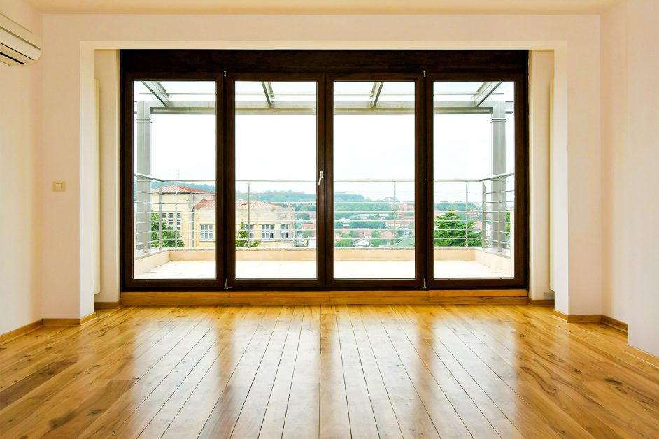 Image of a refinished hardwood floor among massive windows