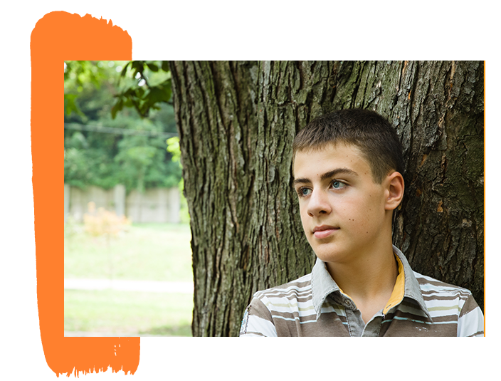 An image of a teen boy leaning against a tree