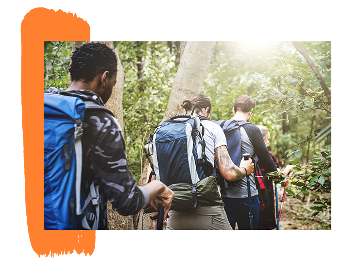 Image of three teens hiking through a forest