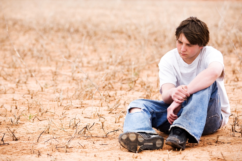 Image of a depressed-looking teen boy sitting isolated in a field