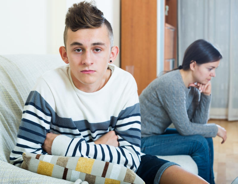 Image of a teen boy sitting on a couch with his mother who looks worried