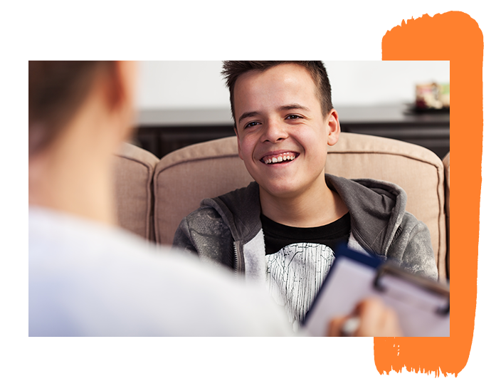 An image of a teen boy laughing during a meeting with a counselor