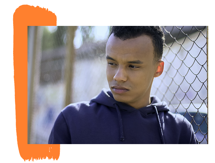An image of a teen boy leaning on a fence looking distraught