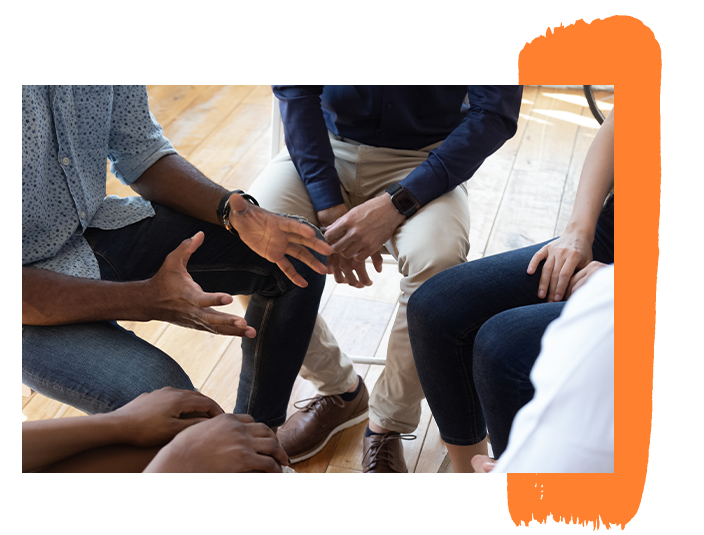 Image of several young men sitting in a circle during a counseling session