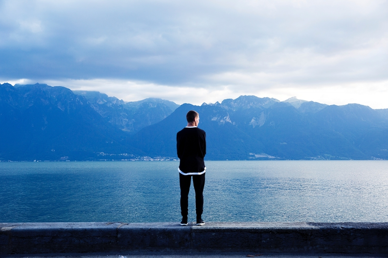 Image of a teen boy standing alone looking out at a lake