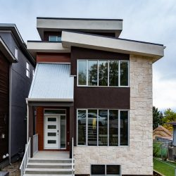 Modern home's exterior with large windows and stairs to front door - Kay2 Contracting