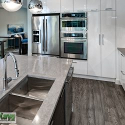 Kitchen renovation with built-in appliances and grey countertops - Kay2 Contracting