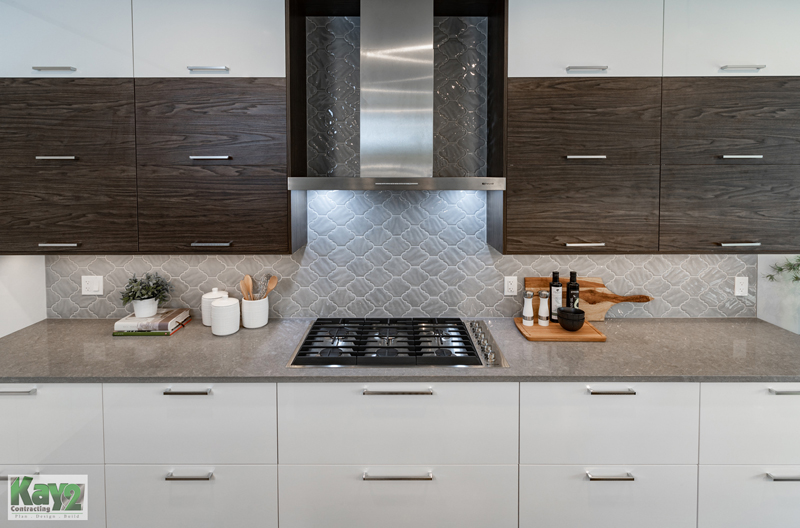 Kitchen with white cabinets on bottom and brown on top and built-in range - Kay2 Contracting