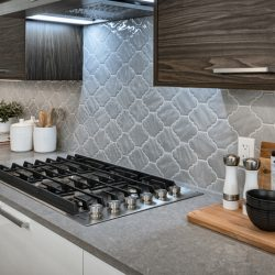 Kitchen with built-in range, grey backsplash, and brown and white cabinets - Kay2 Contracting