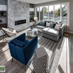 Modern living room after home renovation with large grey feature fireplace - Kay2 Contracting