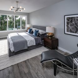 Bedroom with modern lounge chair and large windows - Kay2 Contracting