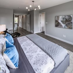View of a master bedroom with bed and doors into the hallway - Kay2 Contracting