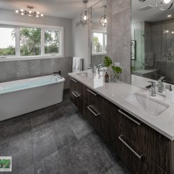 Master bathroom with white countertops, soaker tub, and windows - Kay2 Contracting
