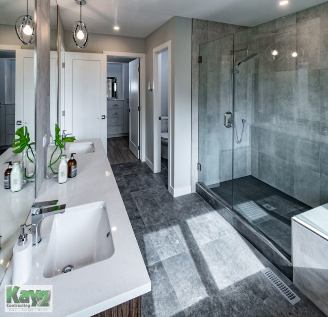 Master bathroom with white countertops, grey tile floors, and large glass shower - Kay2 Contracting