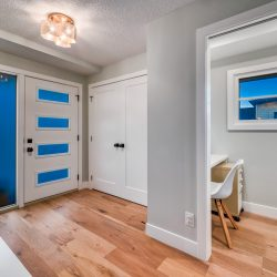 Entryway with light wood floors, closet, entryway door, and view into home office - Kay2 Contracting