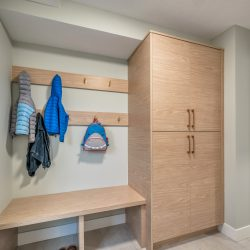 Entryway with bench, storage cabinet, and coats hanging from hooks - Kay2 Contracting