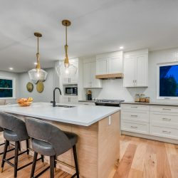 View of kitchen island with light wood cabinets and floors, and three chairs - Kay2 Contracting