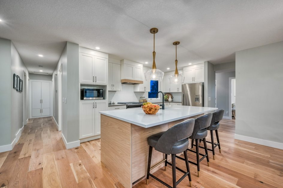 Kitchen with light wood floors and island cabinets and white wall cabinets - Kay2 Contracting