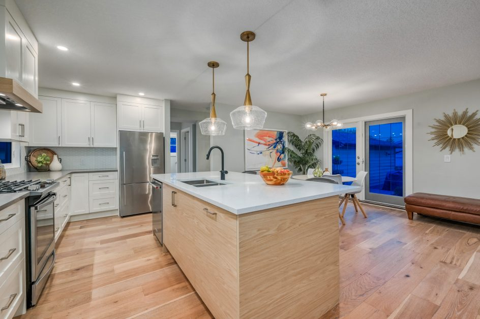 Kitchen with white countertops and light wood island cabinets, light wood floors - Kay2 Contracting