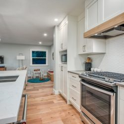 Kitchen with white countertops and cabinets and view of a kid's play area - Kay2 Contracting