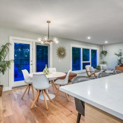 View from kitchen to the open concept living and dining room with wood floors and windows - Kay2 Contracting