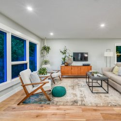 Living room with light wood floors, large picture windows, and modern design - Kay2 Contracting