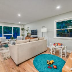 Living room with kid's play area and wood floors - Kay2 Contracting