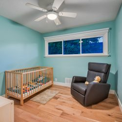 Kid's room with crib and lounge chair in a home remodel - Kay2 Contracting