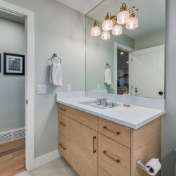 Bathroom renovation with white countertop, wood tone cabinet, and entry to hallway - Kay2 Contracting
