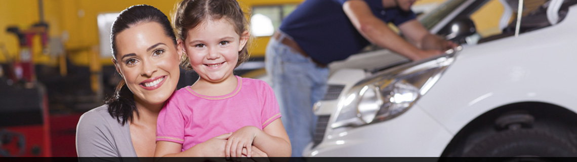 Image of a woman and daughter smiling in front of their car being fixed