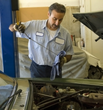 Image of mechanic checking oil levels inside of a vehicle
