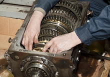 Image of mechanic with hands inside of an engine