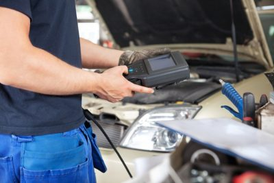 Image of mechanic measuring battery life on a vehicle