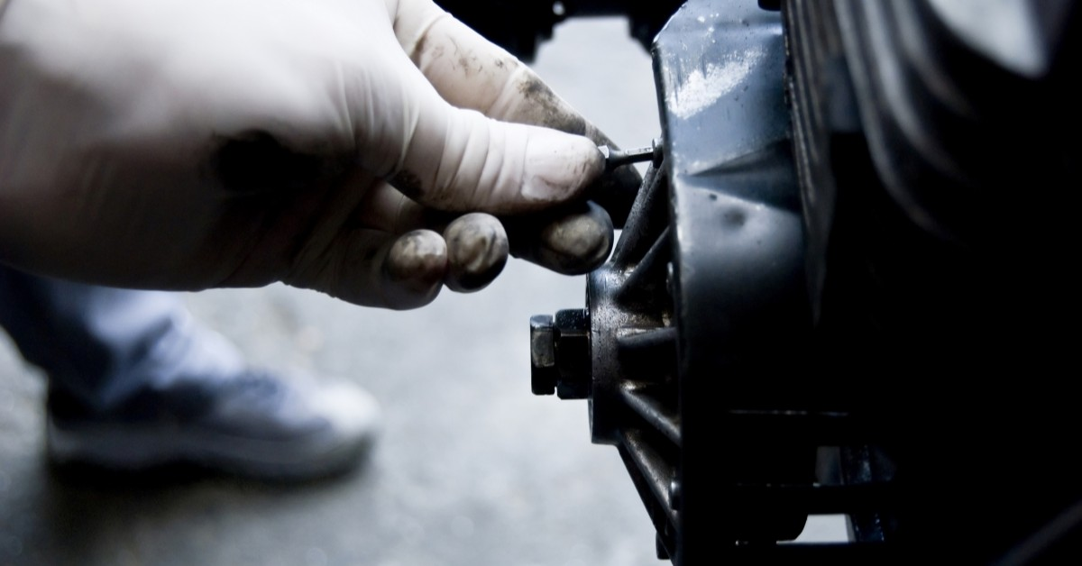 Mechanic Hand Tuning Up Engine