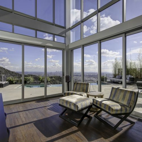 Photo of a living room and wall of windows with view to Los Angeles - Keeprshots