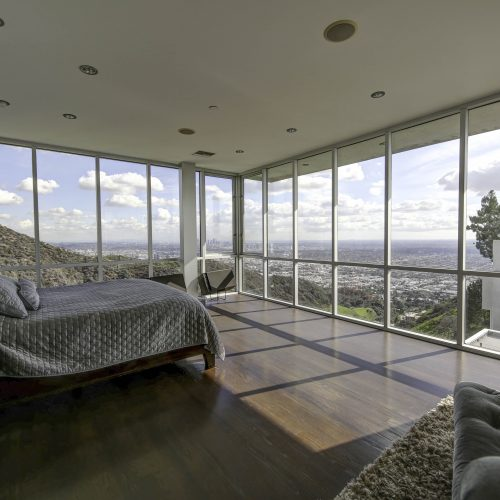 Real estate photograph of a bedroom and view of Los Angeles - Keeprshots