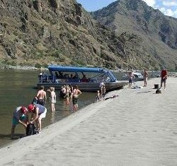 People wading in the water by the jet boat in Hells Canyon