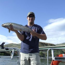 a man holding a salmon he caught in Hells Canyon
