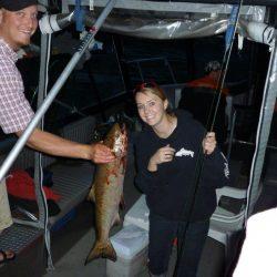 a man holding a salmon near a woman's face