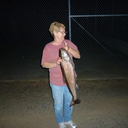 a woman holding a salmon at night