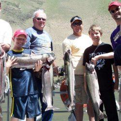 four men and three boys holding salmon