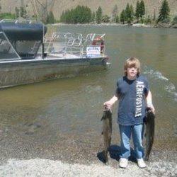 a boy holding a salmon