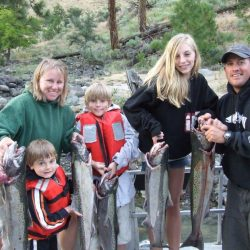 two parents and their three children holding five salmon