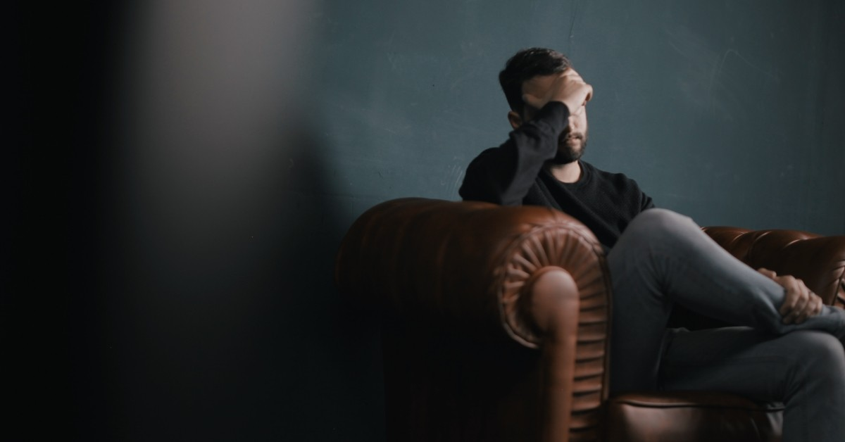 Image of a man with his head in his hands and sitting on a couch.