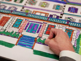 Man's hand drawing coloring in an illustration of a building.