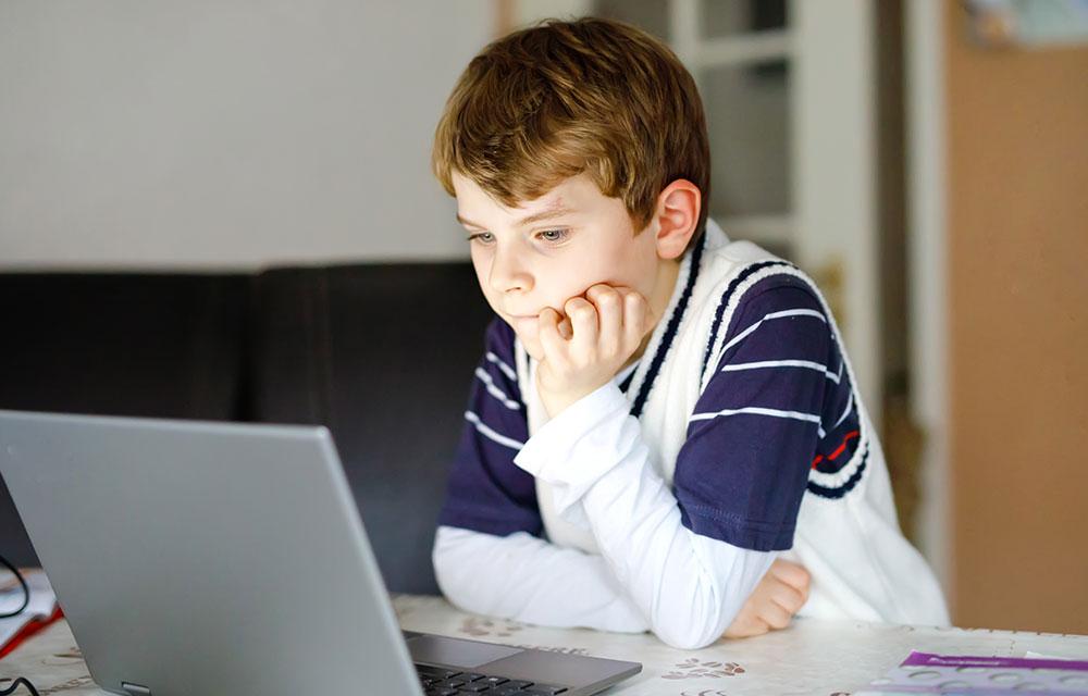 school age boy using laptop