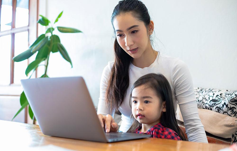 Asian woman and toddler using laptop