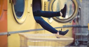 A woman's legs poke out of a large industrial clothes dryer. She wears blue jeans and black tennis shoes.