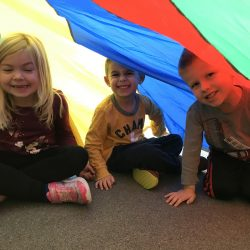 Playing under the parachute at our Rosemount daycare