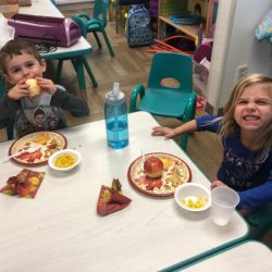 A picture of two toddlers eating breakfast - Leaps and Bounds